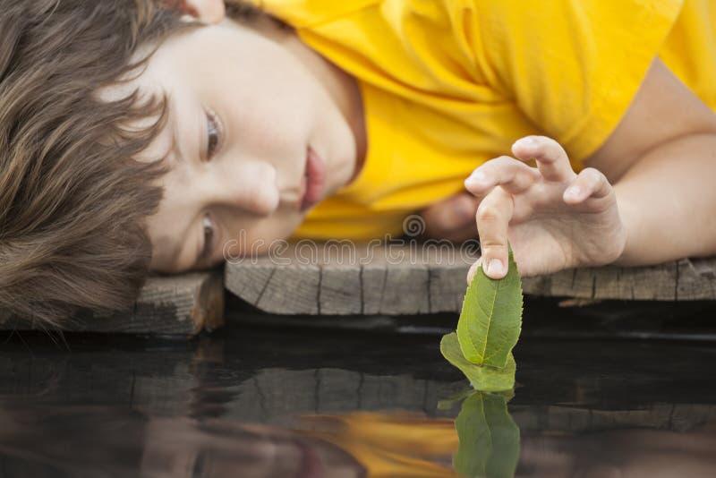 Grünes Blattschiff in der Kinderhand im Wasser, Junge im Parkspiel mit stockbilder