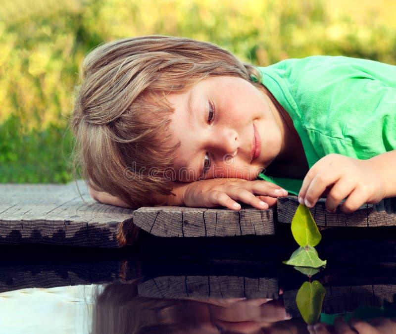Grünes Blattschiff in der Kinderhand im Wasser, Junge im Parkspiel mit Boot im Fluss stockbild
