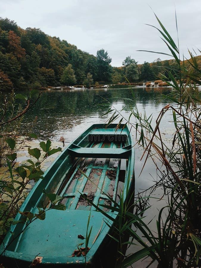 Grünes Boot in einem Fluss stockfotos