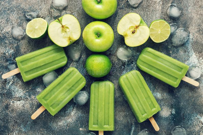 Grünes Eis am Stiel auf einem rustikalen Hintergrund mit Apfel und Kalk Auffrischungsnachtisch des Sommers Flache Lage, Ansicht v lizenzfreie stockbilder