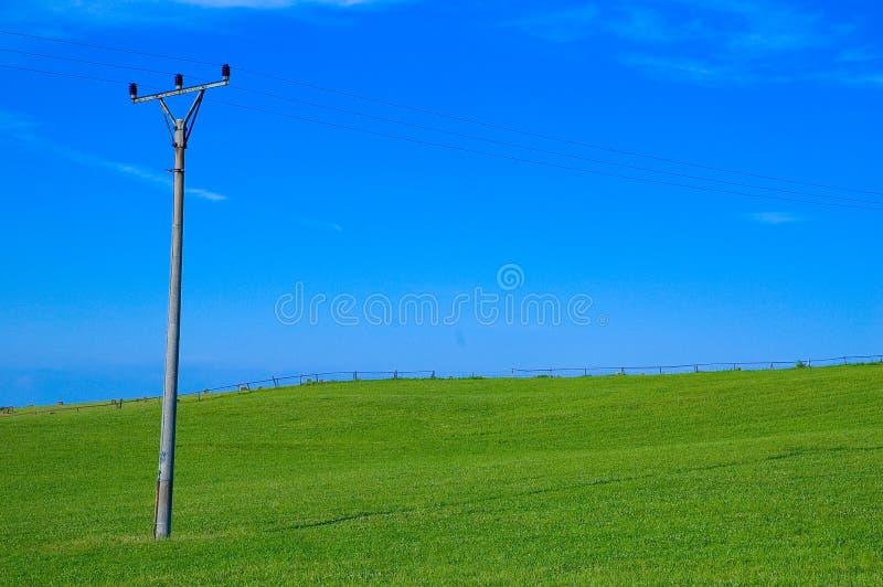 Grünes Feld und Stromleitung Pol lizenzfreie stockfotografie