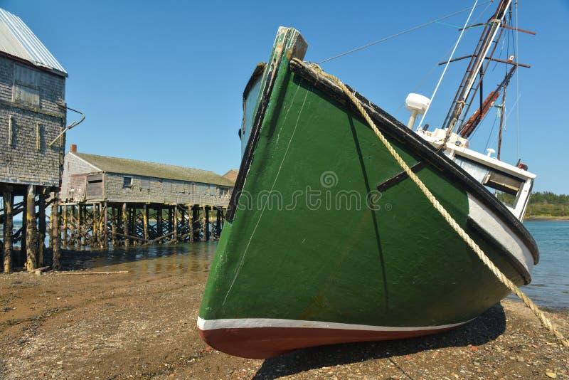 Grünes Fischerboot, das auf SeitenEbbe legt stockbild