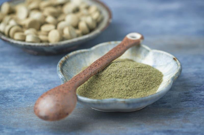 Grünes GERSTEN-GRAS-Biopulver und -tabletten Konzept für eine gesunde diätetische Ergänzung stockbild