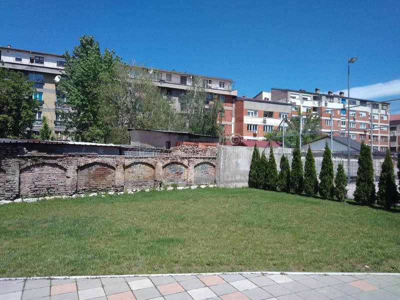 Grünes Gras, Backsteinmauer und Gebäude hinten in Pirot, Serbien lizenzfreie stockfotografie