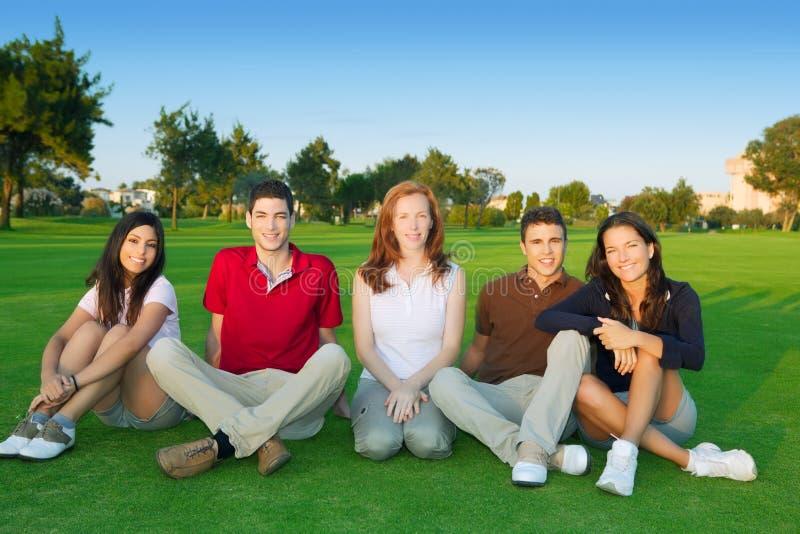 Grünes Gras des glücklichen Sitzens der Freundgruppenleute lizenzfreies stockbild