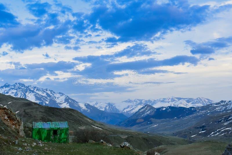 Grünes Häuschen in einer Berglandschaft bei Sonnenuntergang lizenzfreies stockfoto