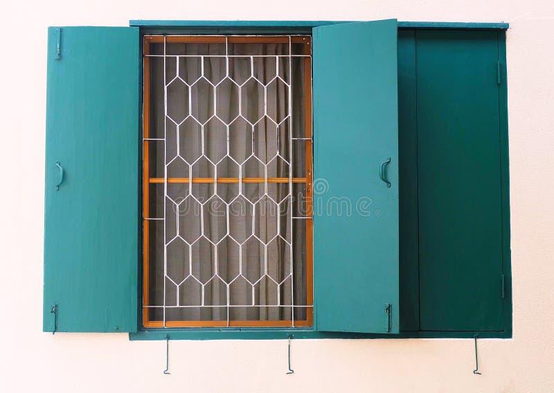 Grünes hölzernes Fenster mit Metallgrill auf der Wand stockfotografie