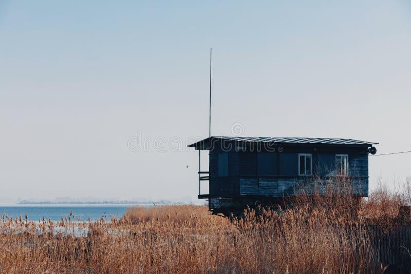 Grünes Haus auf dem Ufer von einem großen See Bootsstation unter Gras und Wasser lizenzfreie stockfotos