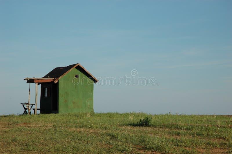 Grünes Haus auf einem grünen Feld stockbild