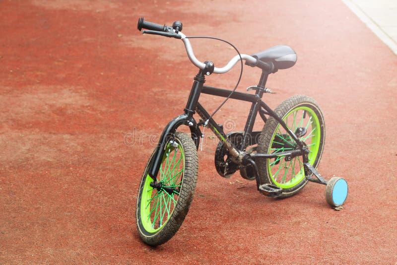Grünes Kind-` s Fahrrad bei Sonnenuntergang lizenzfreies stockbild