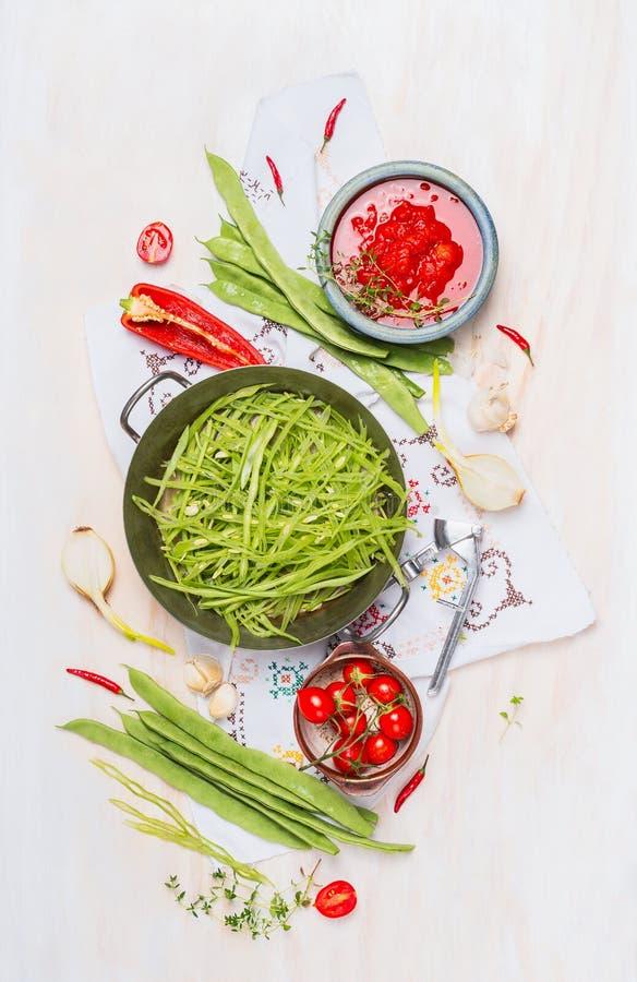 Grünes Kochen der grünen Bohnen Geschnittene grüne grüne Bohnen, wenn Teller und Bestandteile auf weißem hölzernem Hintergrund, D stockbild