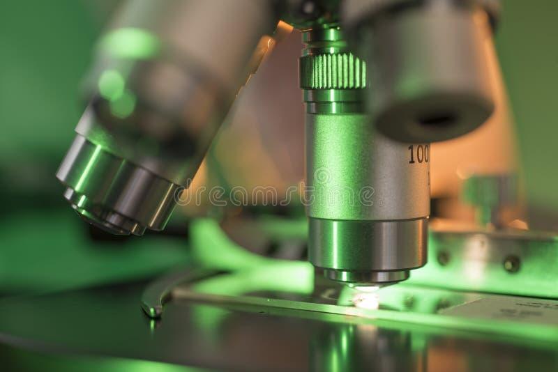 Grünes Licht, das auf Mikroskop-Linse fällt lizenzfreie stockbilder