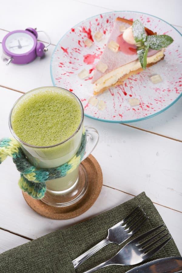 Grünes macha Teeglas gedient mit dem Käsekuchen gedient auf hölzernem Brett stockbilder