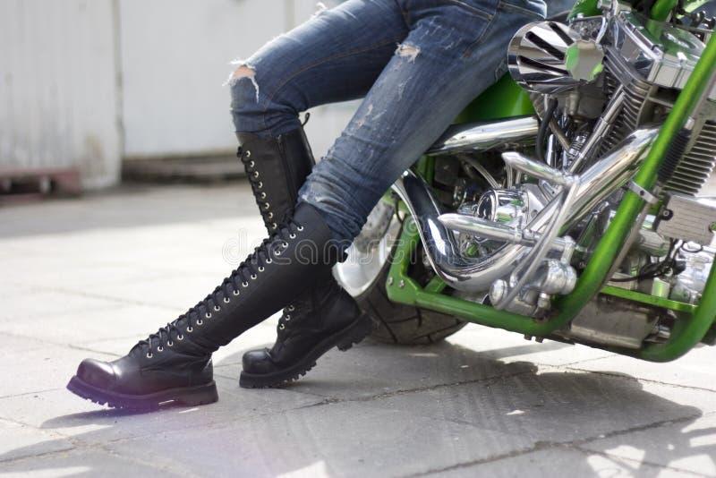 Grünes Motorrad und eine Frau in den schweren Matten stockbilder