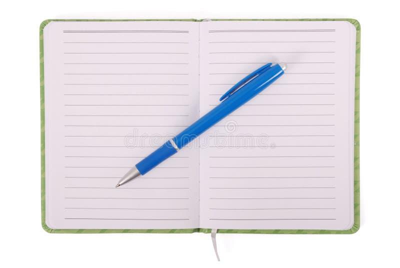 Grünes Notizbuch und blauer Griff lizenzfreies stockbild