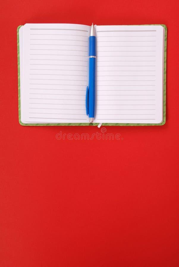 Grünes Notizbuch und blauer Stift stockbild