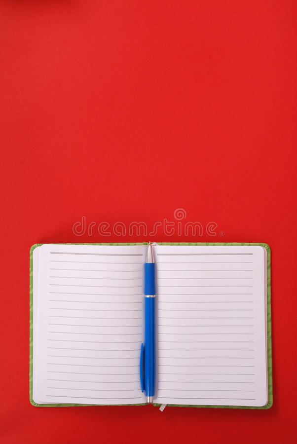 Grünes Notizbuch und blauer Stift lizenzfreie stockfotos
