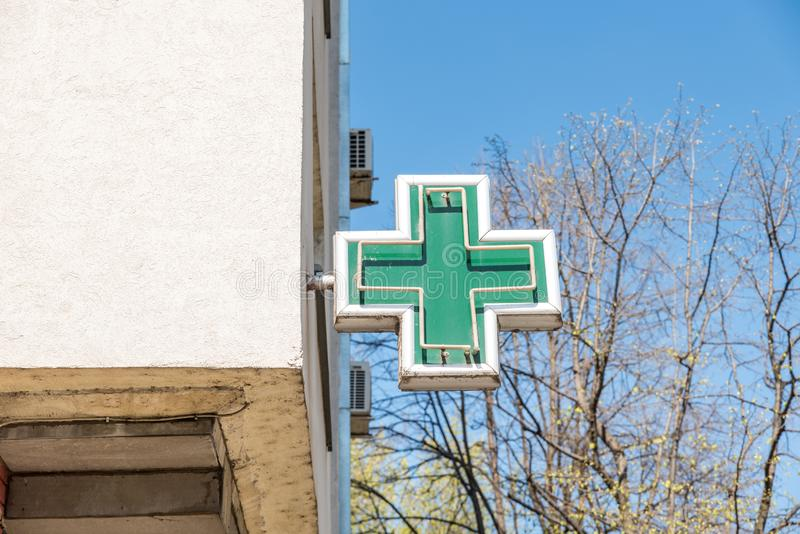 Grünes Querapothekenzeichen oder -symbol auf der Gebäudefassadenansicht von der Straße lizenzfreie stockfotografie