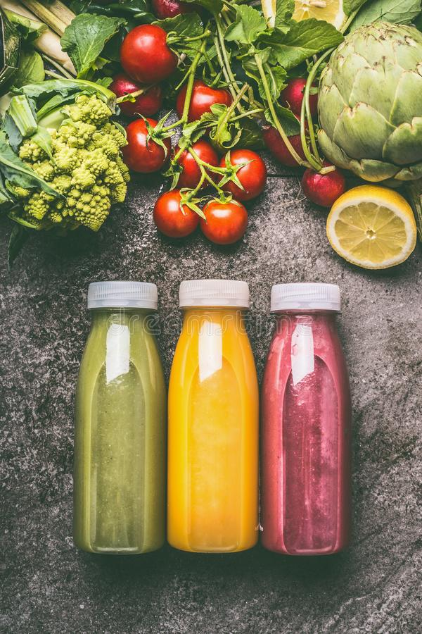 Grünes, rotes und gelbes buntes organisches Gemüse, Früchte und Beeren Smoothies mit Bestandteilen in den Flaschen auf grauem Gra stockbilder