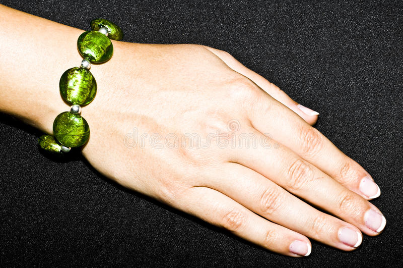 Grünes Smaragdarmband auf Frauenhand stockfotografie
