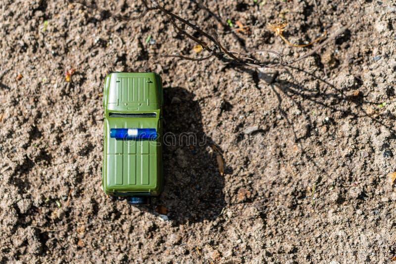Gr?nes Spielzeugauto mit blauer Lampe auf dem Dach auf dem Grundhintergrund Die Ansicht von der Oberseite Kopieren Sie Platz Weic stockbilder