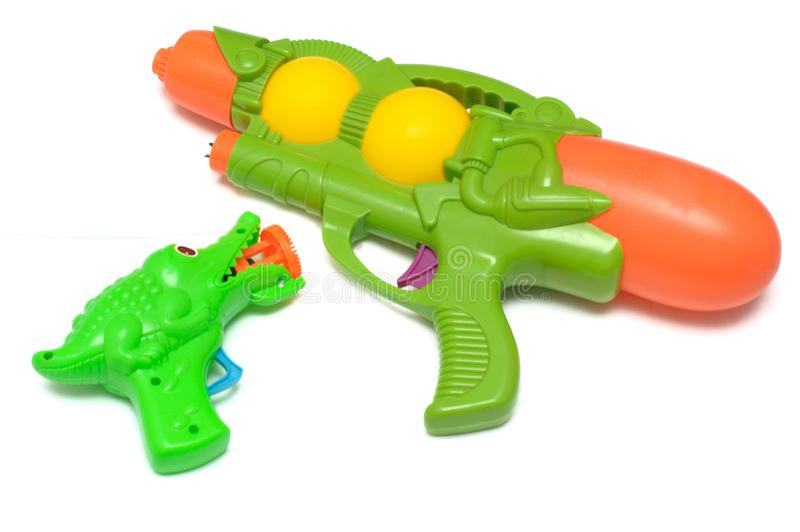 Grünes Spielzeugwasser und -ton schießen gegen einen weißen Hintergrund stockfotografie