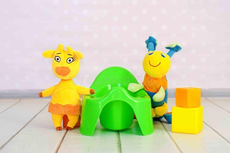 Grünes Töpfchen und Spielwaren auf Hauptinnenhintergrund stockbilder