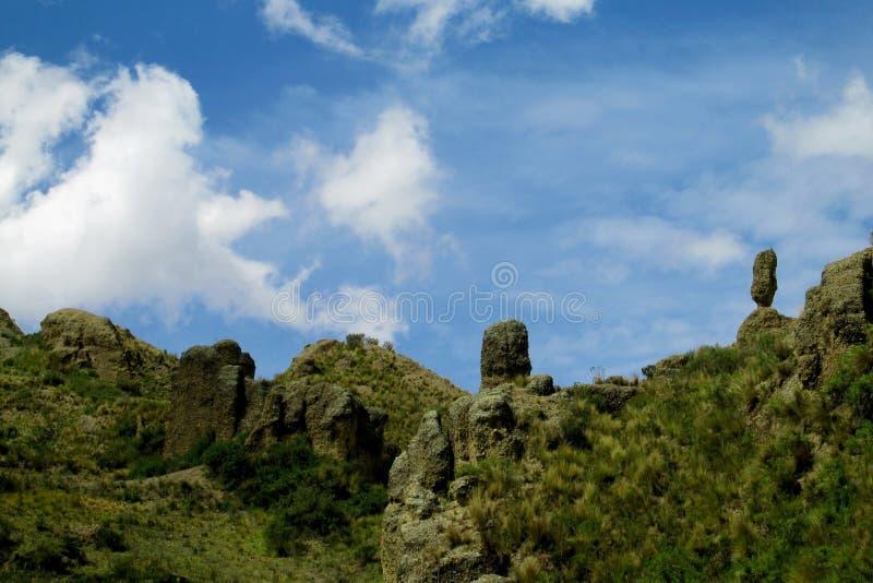 Grünes Tal und Felsformationen unter blauem Himmel lizenzfreie stockfotografie