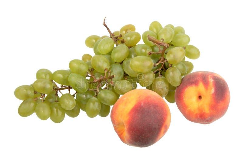 Grünes Traubenbündel und Pfirsich mit zwei Orangen. stockbilder