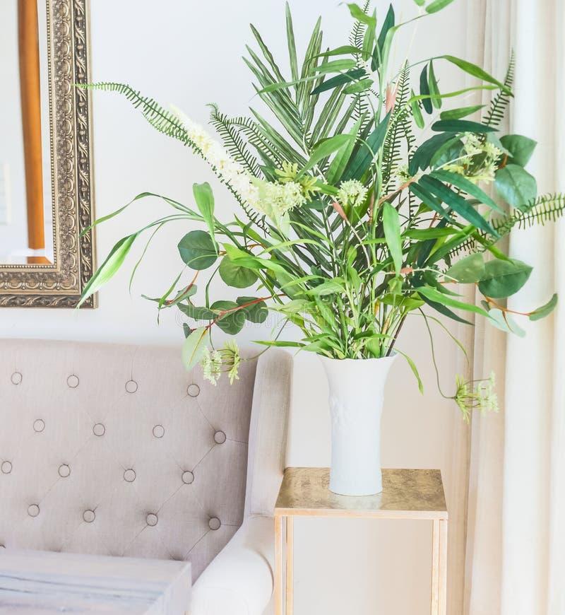 Grünes tropisches Houseplantsbündel im Vase nahe der Couch im Luxuswohnzimmer Glaskerzen, Oberteile und Anlagen stockfotografie