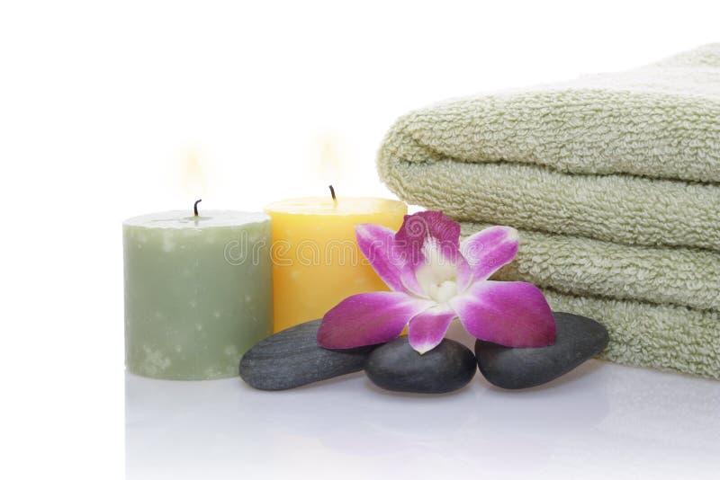 Grünes Tuch, Orchidee, Kerze und Kiesel stockfotografie