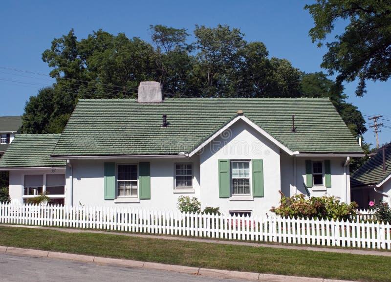Grünes u. weißes Häuschen mit weißem Palisadenzaun lizenzfreie stockfotografie