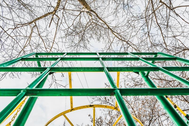 Grünes und gelbes Metallkletterndes Gitter gegen blauen Himmel mit weißen Wolken und Pappel- und Ahornbaumniederlassungen auf dem lizenzfreie stockfotos