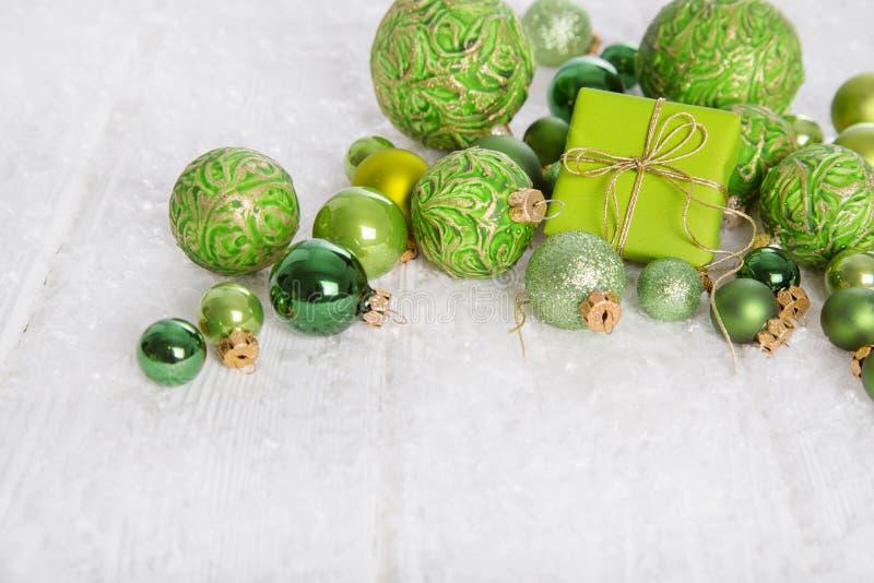 Grünes und weißes Weihnachtshintergrund mit Geschenkbox, Schnee und bal lizenzfreie stockfotos