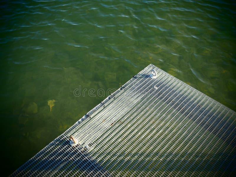 Grünes Wasser mit dem Rand einer Metallplattform lizenzfreies stockfoto