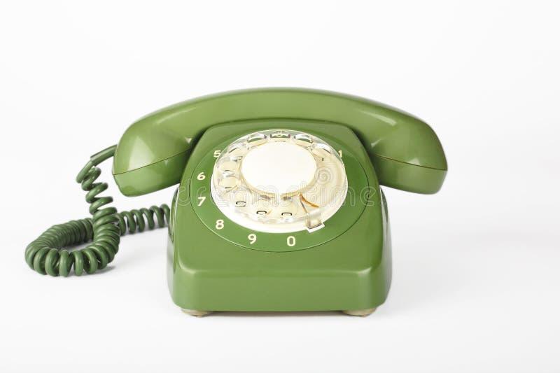 Grünes Weinlesetelefon auf einem weißen Hintergrund stockbilder