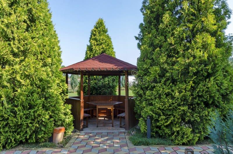 Grünes Yard der Schönheit mit Nische mit der Tabelle hölzern und Bank für Rest stockbild