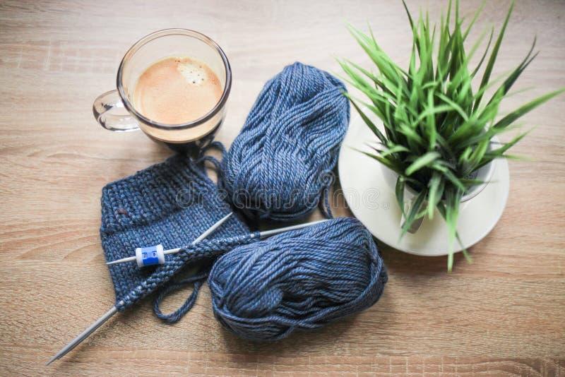 Grünpflanze im Topf, Stricknadeln, blaues Garn und schwarzer Kaffee sind auf dem Tisch stockfotos