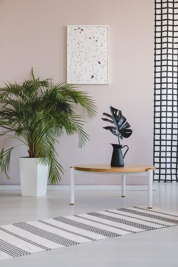 Grünpflanze im weißen Topf nahe bei Kaffeeholztisch mit schwarzem Blatt im schwarzen Vase, wirkliches Foto mit Plakat auf leerer  lizenzfreie abbildung
