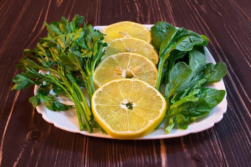 Grüns und Zitronenlüge auf einer Platte lizenzfreie stockfotografie