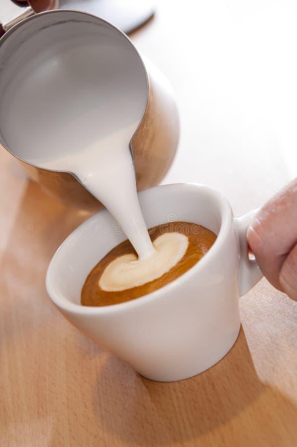 Grże Dojnego lub Kremowego dolewanie w filiżankę kawa espresso zdjęcie royalty free
