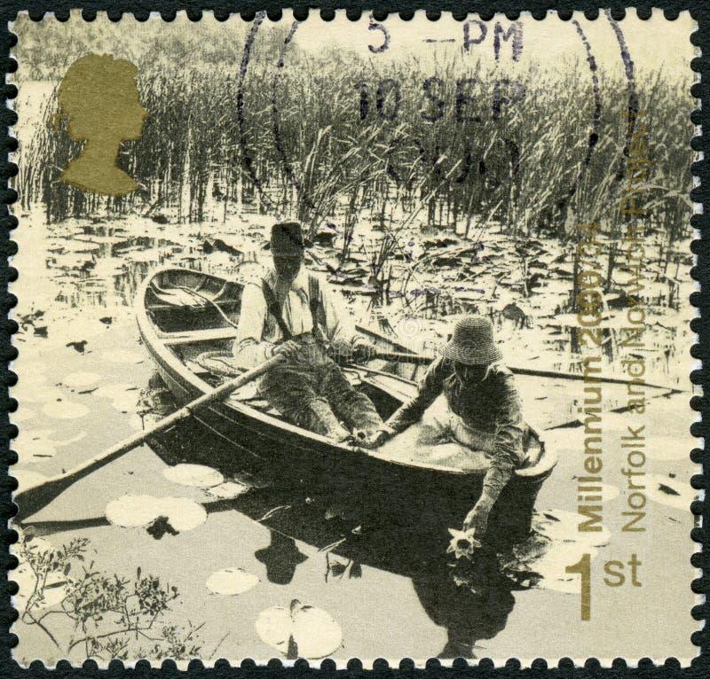 GRÂ BRETANHA - 1999: mostra povos no barco a remos, o projeto de Norfolk e de Norwich, o Newport, o milênio 2000 da série, a ment fotos de stock royalty free