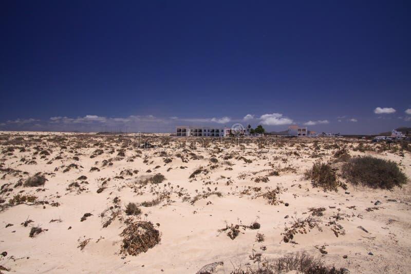 Gr Cotillo - Faro del Toston: Weergeven over duinen op hotel buildung tegen blauwe hemel royalty-vrije stock foto