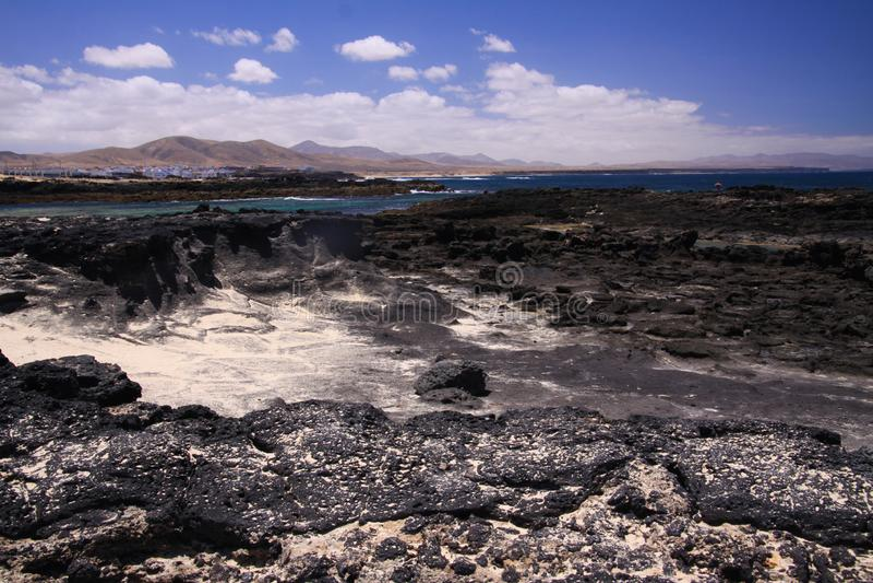 Gr Cotillo - Faro del Toston: Weergeven over zwarte vulkanische rotsen en lagune op dorp van het noorden Fuerteventura van strand royalty-vrije stock afbeelding