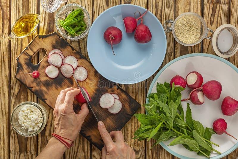 Gr?n gr?nsak, vegetariskt organiskt, handsnitt, sund mat, nya gr?nsaker, platta, hemmafru som skivar, organisk mat som lagar mat  arkivfoto