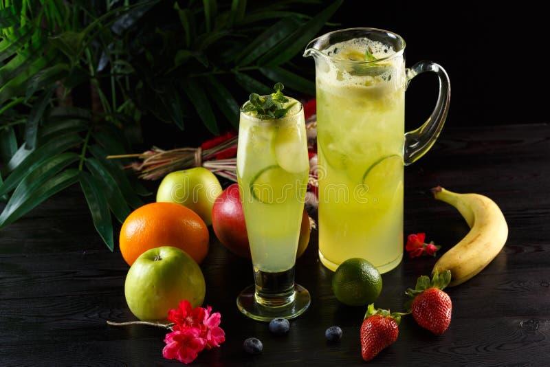 Gr?n ?pplelemonad med limefrukt i en tillbringare och ett exponeringsglas och frukter p? en m?rk bakgrund arkivbilder