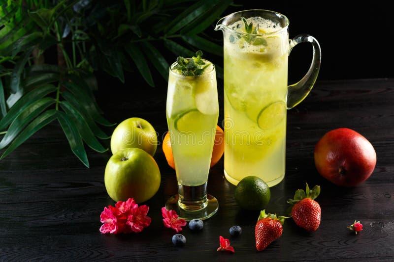 Gr?n ?pplelemonad med limefrukt i en tillbringare och ett exponeringsglas och frukter p? en m?rk bakgrund royaltyfria foton