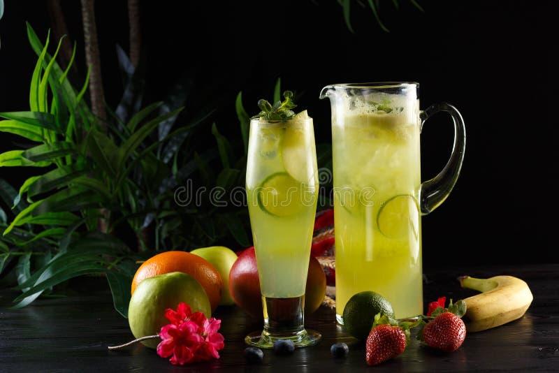 Gr?n ?pplelemonad med limefrukt i en tillbringare och ett exponeringsglas och frukter p? en m?rk bakgrund arkivfoton