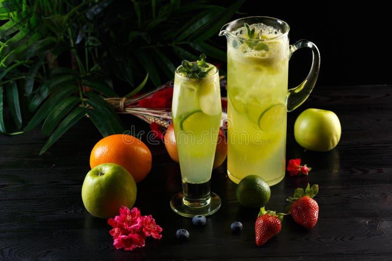 Gr?n ?pplelemonad med limefrukt i en tillbringare och ett exponeringsglas och frukter p? en m?rk bakgrund fotografering för bildbyråer