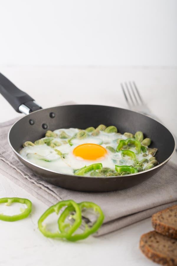 Gr?n shakshuka Stekte ägg med ny peppar, bönor på en grå bakgrund, lantlig stil royaltyfri fotografi